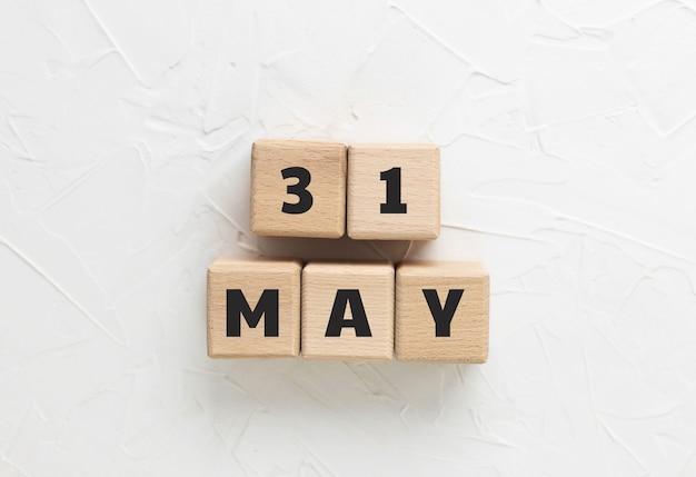 Текст 31 мая сделан из деревянных кубиков на белом текстурированном фоне шпатлевки. день памяти 2021 года. американский праздник. почитание и оплакивание военных. квадратные деревянные блоки. вид сверху, плоская планировка. Premium Фотографии