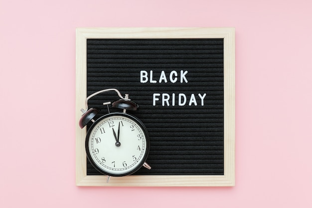 Text black friday on black letter board and alarm clock on pink background. concept black friday , season sales time Premium Photo