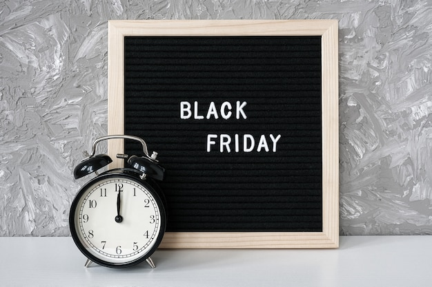 Text black friday on black letter board and alarm clock on table Premium Photo