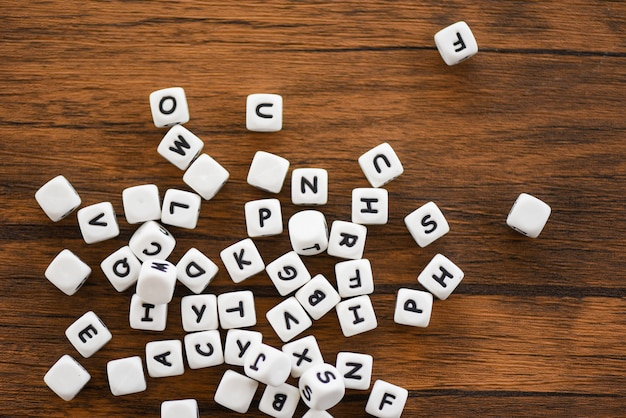 Text dice cube concept - letter dices alphabet on wooden background Premium Photo