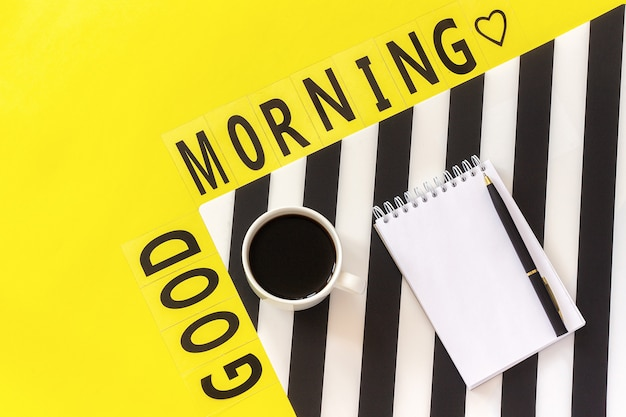 Text good morning, coffee, notebook for text on stylish black and white napkin on yellow background. concept good morning Premium Photo