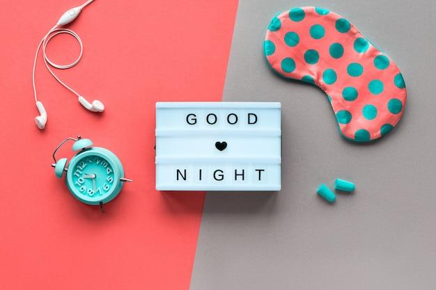 Текст «спокойной ночи» здоровый ночной сон креативная концепция. спальная маска в горошек, будильник, наушники и беруши. плоская планировка, вид сверху, двухцветная коралловая стена и бирюзовая бумага. Premium Фотографии