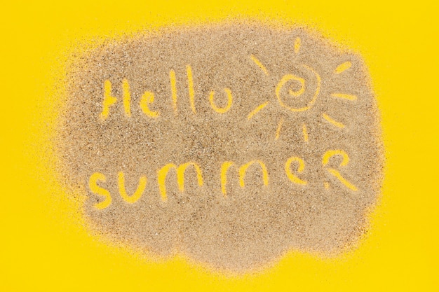 Text hello summer and sun sign drawn on sand on yellow paper background concept vacation Premium Photo