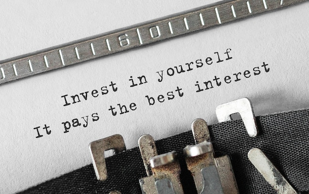 Text invest in yourself, it pays the best interest typed on retro typewriter Premium Photo