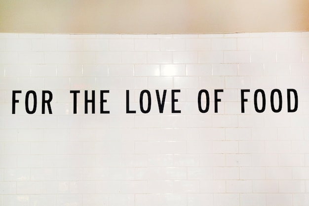 Text for the love of food on white wall Free Photo