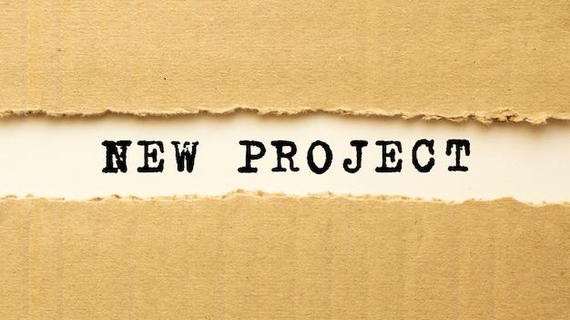 Текст новый проект появляется за рваной оберточной бумагой. вид сверху. Premium Фотографии