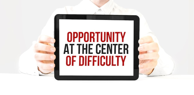 Text opportunity at the center of difficulty on tablet display in businessman hands on the white bakcground. business concept Premium Photo