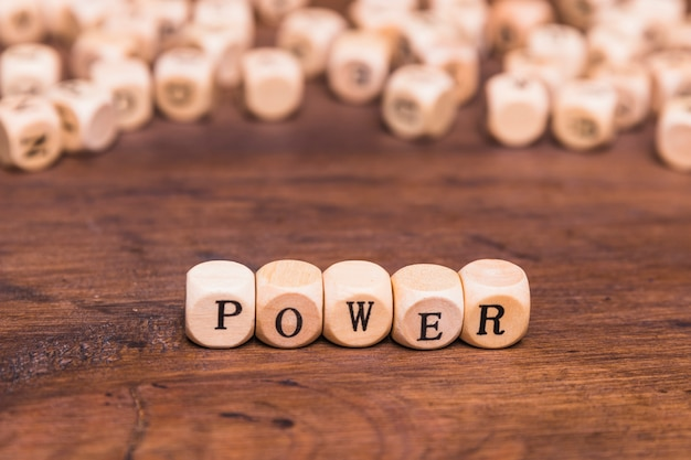 Text power written on wooden dices over brown desk Free Photo