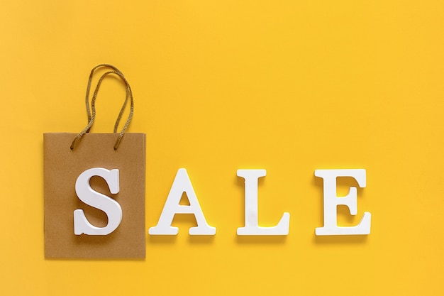 Text sale from white volume letters and blank shopping bag on yellow background. Premium Photo