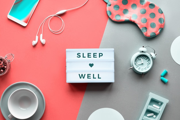 Текст «спи спокойно» на модном лайтбоксе. таблетки, капсулы и успокаивающий чай. плоская планировка, оранжевый коралловый и серебряный фон. коралловая маска для сна с горошком, будильником, наушниками и затычками для ушей. Premium Фотографии