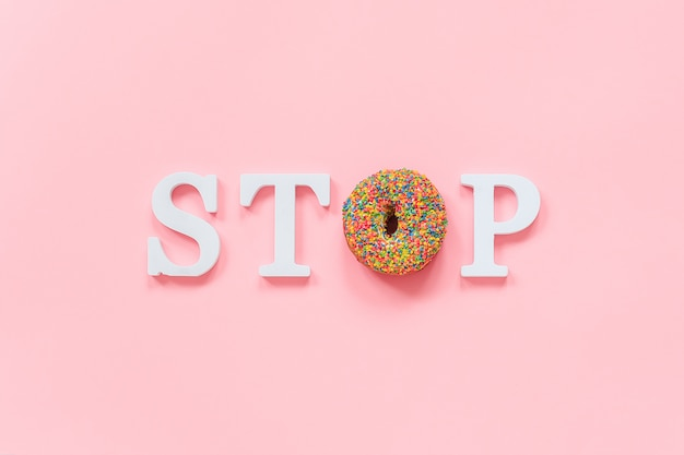 Text stop from white volume letters and glazed colorful donut diet, refusal of fast food, unhealthy food Premium Photo