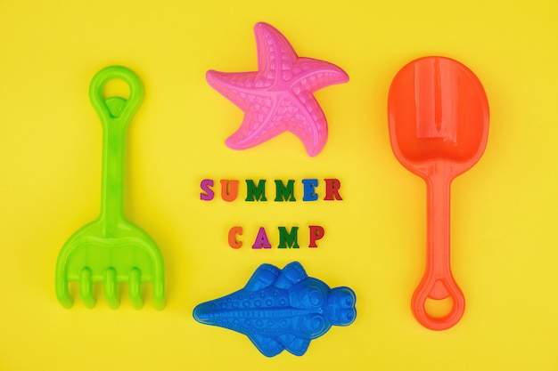 Text summer camp and childrens toys for summer games in sandbox or on sandy beach Premium Photo