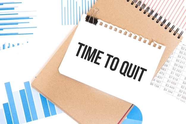Text time to quit on white paper sheet and brown paper notepad on the table with diagram Premium Photo