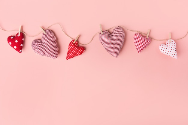 Textile valentines day hearts on pink Free Photo