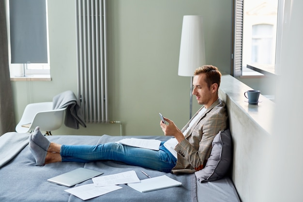 Texting with colleague on smartphone Free Photo