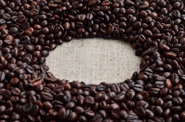 Texture of a gray canvas made of old and coarse burlap with coffee beans on it Premium Photo