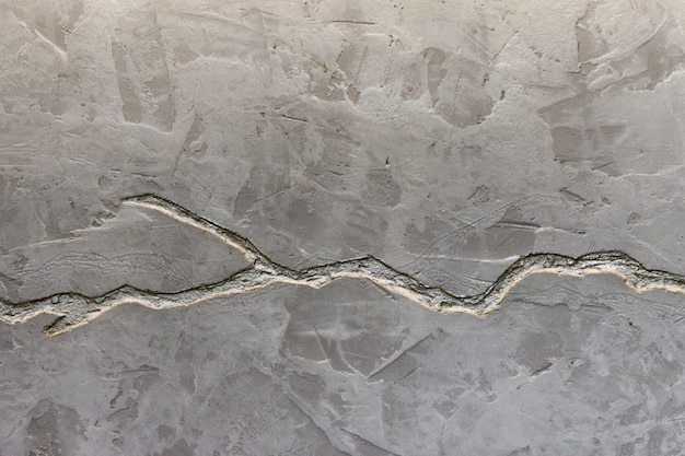 The texture of the gray concrete wall is decorated with a deep crack of silver color. Premium Photo