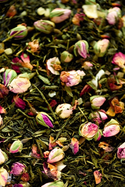 Texture of green tea with rose petals. dried rosebuds texture closeup. food. organic healthy herbal leaves, detox tea. Premium Photo