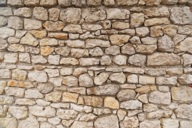 Texture of medieval old light colored stone wall. Premium Photo