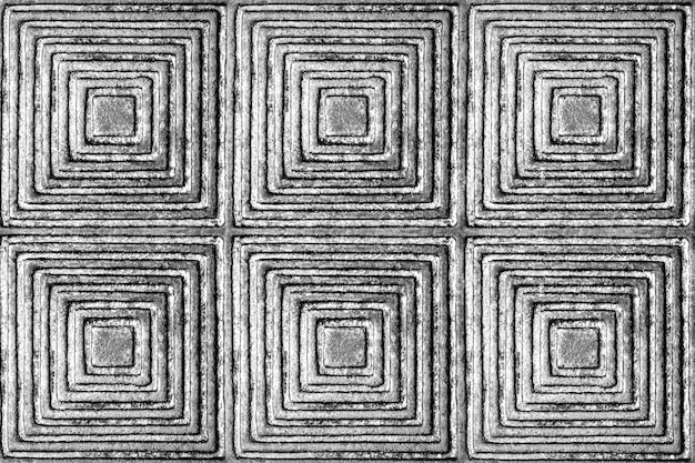 The texture of a metal surface with a pattern in the form of squares and rhombuses in black and white. Premium Photo