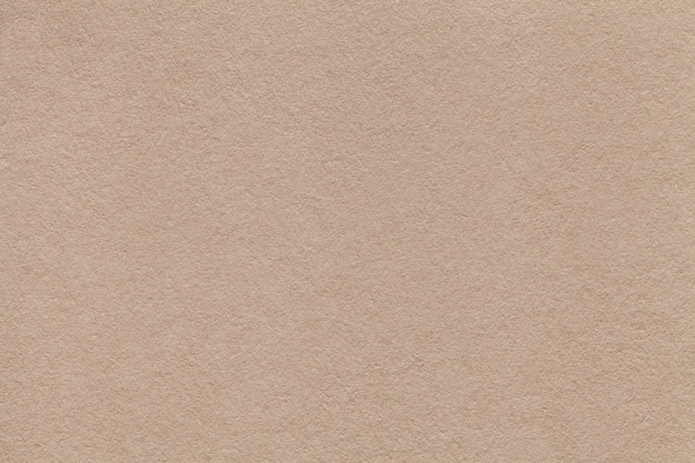 Texture of old beige paper closeup. structure of a dense cardboard sand color. the background. Premium Photo