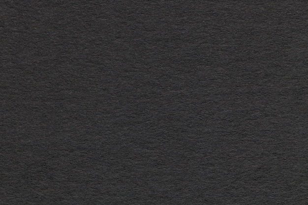 Texture of old gray paper closeup. structure of a dense cardboard. the black background. Premium Photo