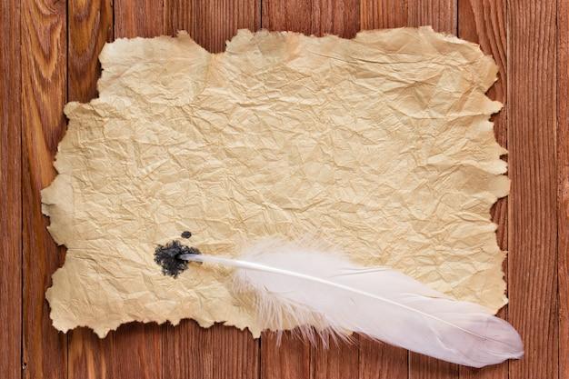Tekstur kertas tua dan bulu putih di atas meja Foto Premium