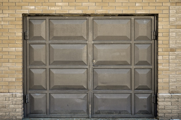 The texture of a painted metal gate from a brick garage Premium Photo