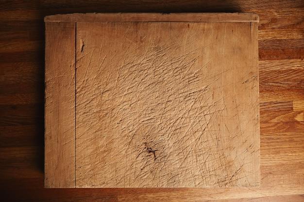 Texture di un tagliere molto vecchio e molto usato con tagli profondi su un bellissimo tavolo in legno marrone Foto Gratuite