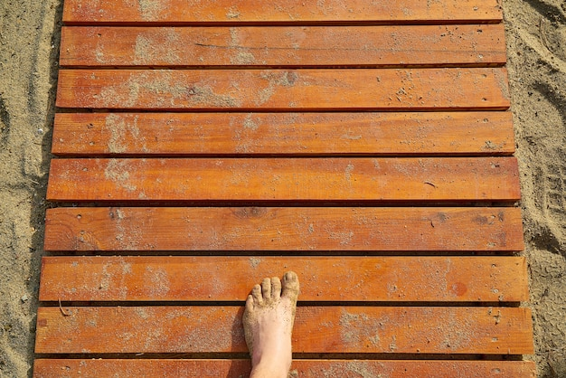 Texture of wooden boards with sand and a foot Free Photo