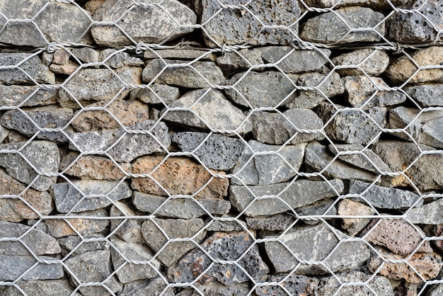 Textured Background Of Gabion, Rock Wall With Wire Meshed Fence