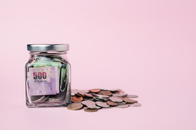 Thai currency banknote and coins in the glass jar for business, finance, investment and saving money concept Premium Photo