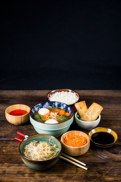 Thai fish ball soup; spring rolls; beans sprout and sauce with chopsticks on wooden desk against black backdrop Free Photo