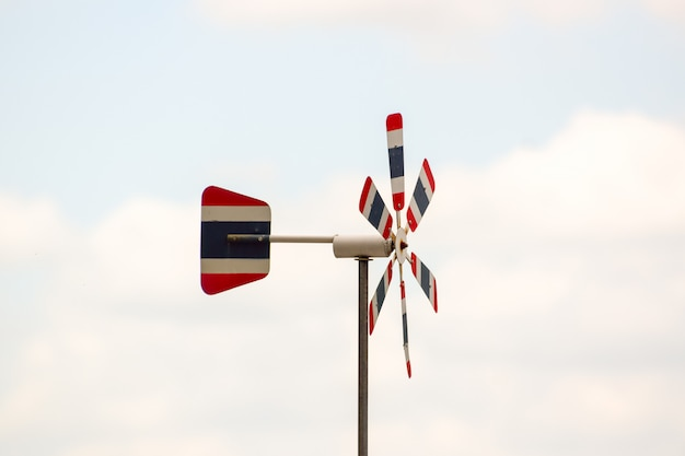 Thai flag wind turbine, blurred natural sky color, the wind blows through, causing the propeller to rotate, free space in the image Premium Photo