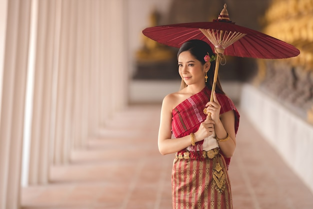 Thai girl in traditional thai costume with red umbrella in thai temple, identity culture of thailand. Premium Photo