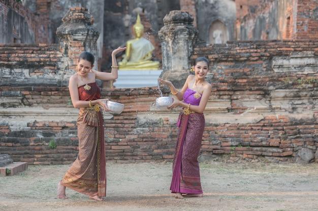 Thai girls in thai traditional dress splashing water during festival songkran festival, ayutthaya, thailand. Premium Photo