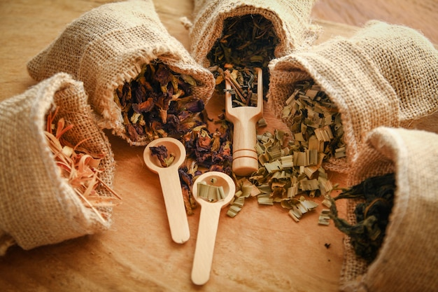 Thai herb set in a brown sack bag, several bags with a spoon placed on the wood floor Premium Photo