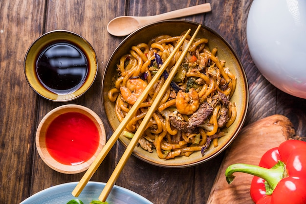 Thai pad with vegetable; king prawns and beef with soya sauce on wooden table Free Photo
