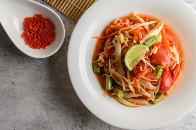 Thai papaya salad in a white plate and dried shrimp Free Photo