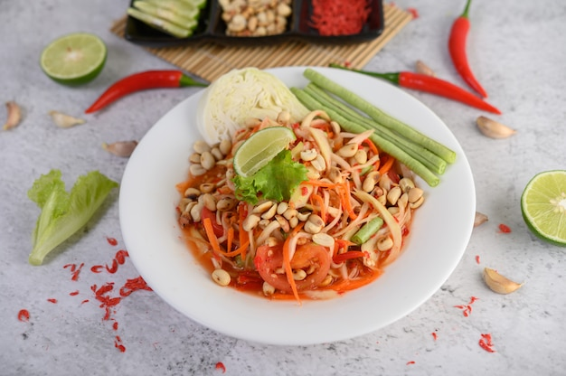 Thai papaya salad in a white plate with chili, lime, and garlic. Free Photo