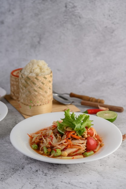 Thai papaya salad in a white plate with sticky rice Free Photo