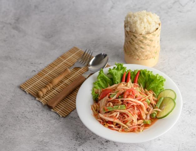 Insalata tailandese della papaia in un piatto bianco con riso appiccicoso Foto Gratuite