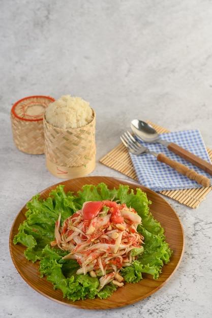 Insalata tailandese della papaia in un piatto di legno con la coltelleria Foto Gratuite