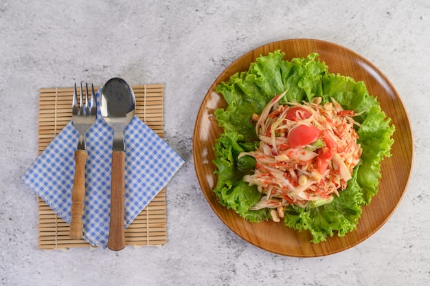 Thai papaya salad in a wooden plate with cutlery Free Photo