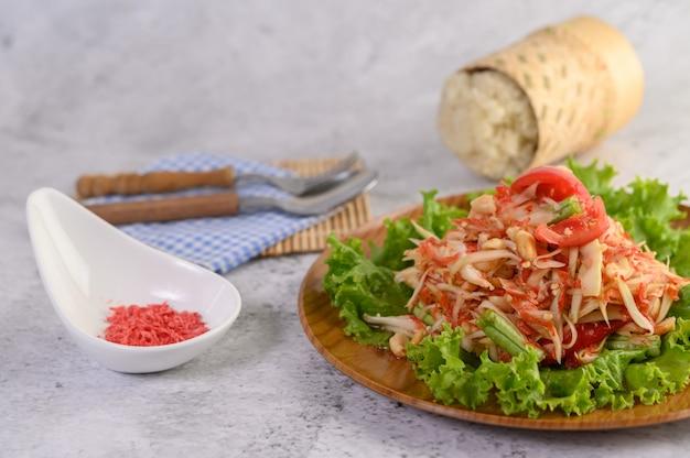 Insalata tailandese della papaia in un piatto di legno con riso appiccicoso e gamberetto essiccato Foto Gratuite