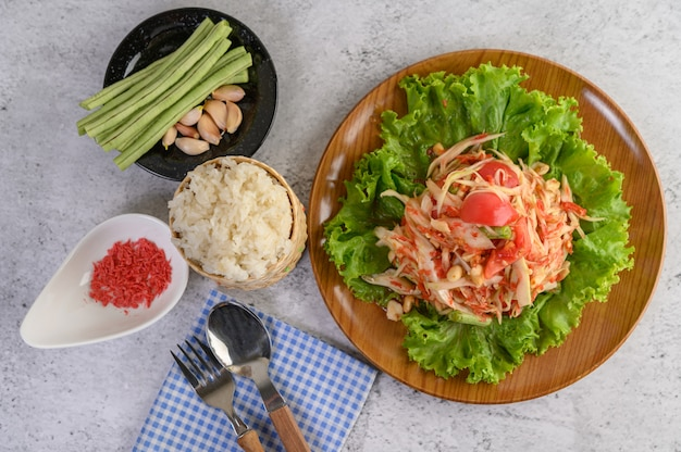Thai papaya salad in a wooden plate with sticky rice Free Photo