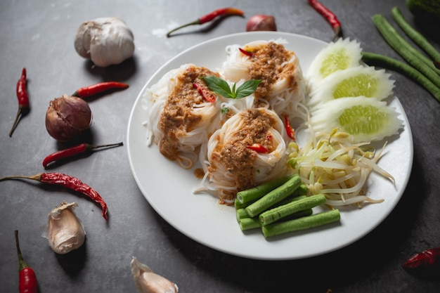 Thai rice noodles in fish curry sauce on wooden table. Free Photo