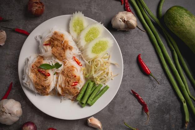 木製のテーブルに魚のカレーソースでタイの米麺。 無料写真