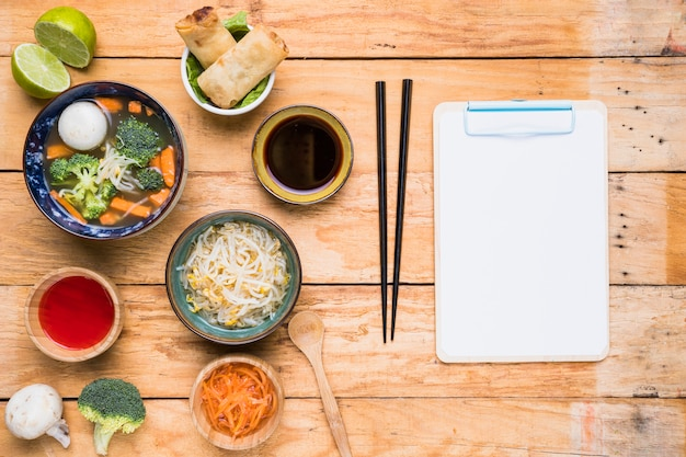Thai soup; spring rolls; sauces and sprout beans with chopstick and white paper on clipboard over the wooden table Free Photo