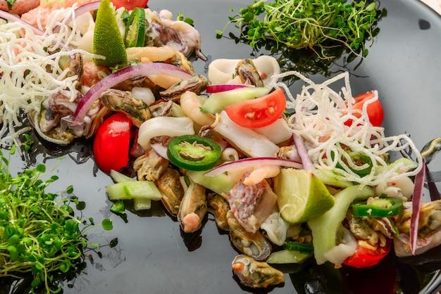 Тайский острый и кислый салат из морепродуктов на деревянном столе Premium Фотографии